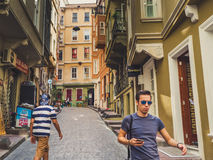 Turkish people and the colorful building. Istanbul, Turkey - September 13 2016: Colorful building in narrow street with people walks royalty free stock image