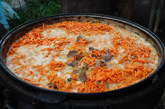 Turkish pilau. Preparing for the wedding table. A huge cauldron of boiling pilaf Stock Images