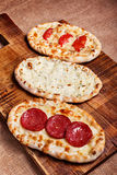 Turkish pita bread. With cottage cheese, chicken, salami and tomatoes on a wooden cutting board. Mini pizzas Stock Images