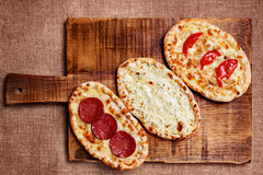Turkish pita bread. With cottage cheese, chicken, salami and tomatoes on a wooden cutting board. Mini pizzas Royalty Free Stock Photography