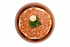 Turkish Pizza Lahmacun. Delicious Turkish pizza lahmacun in clay pan Royalty Free Stock Image