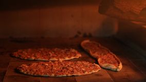Turkish Pizza Lahmacun and pide cooking in wooden oven stock video footage