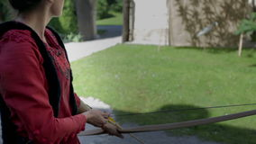 Turkish princess shoots with a bow. On this close up footage is a Turkish princess who is shooting with wooden bow in the middle of the castle on sunny day stock footage