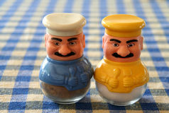 Turkish salt and pepper shakers. Right out of grandma's kitchen! Turkish salt and pepper shakers in yellow and blue on a tablecloth background Royalty Free Stock Images
