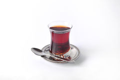 Turkish tea. A glass of Turkish tea on a metal plate with a spoon Royalty Free Stock Images