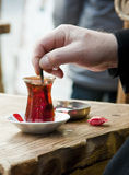 Turkish tea. Man's hand stirring a cup of traditional turkish tea Stock Image
