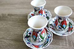 Turkish tea or coffee cups and small plates. Over a light wood grey background stock photography