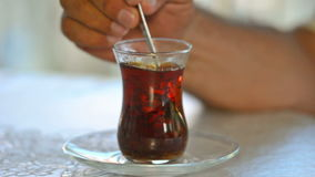 Turkish tea cup. Sugar Droping In To Tea And Mixing It With Spoon stock video