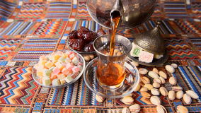 Turkish tea poured from a metal teapot in traditional dishes. On the table sweets and nuts stock video