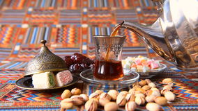 Turkish tea poured from a metal teapot in traditional dishes. On the table sweets and nuts stock footage