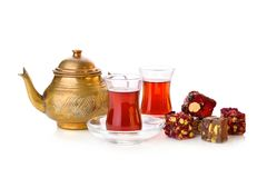 Turkish tea with rahat lokum. Traditional turkish delight rahat lokum with two glasses of tea and teapot on a white background Stock Images