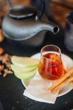 Turkish tea. Served in glass with cinnamon sticks and fruit slices with black kettle on table Royalty Free Stock Image
