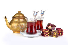 Turkish tea. Traditional turkish delight rahat lokum with two glasses of tea and teapot on a white background Royalty Free Stock Images