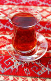 Turkish tea in traditional glass cup. On handmade arabic ornamental tablecloth, travel in Turkey Stock Photo