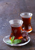 Turkish tea in traditional glass with dates Stock Photo