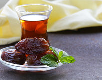 Turkish tea in traditional glass with dates Royalty Free Stock Photography