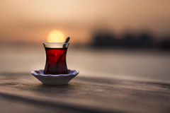 Turkish tea. On a wooden table and the sun is over the glass like a yellow ball Stock Photos