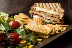 Turkish Toast or Tost / Triangle Club Sandwich with Melted Cheese, Ham and Served with Chips and Salad. Fast Food royalty free stock photo