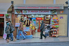 Turkish trader. ISTANBUL - DECEMBER 06: People walking by traditional store with trader in the old traditional suit , on December 06, 2012 in Istanbul, Turkey Royalty Free Stock Photography