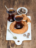 Turkish traditional black tea in a glass and turkish bagel simit on white ceramic serving board over wooden background Stock Images