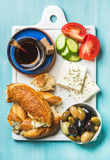 Turkish traditional breakfast with feta cheese, vegetables, olives, simit bagel and tea Stock Photography