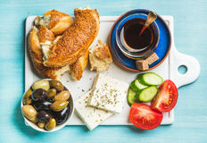 Turkish traditional breakfast with feta cheese, vegetables, olives, simit bagel and tea. On white ceramic board over turquoise blue background. Top view Royalty Free Stock Image