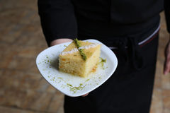 Turkish traditional dessert Revani. On white plate in garsons hand Royalty Free Stock Photography