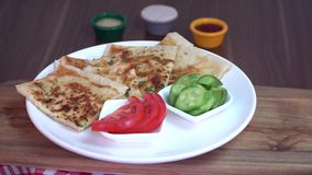 Turkish traditional Gozleme pita potatoes with cucumber and sliced tomato rotating on scotch pattern fabric stock video