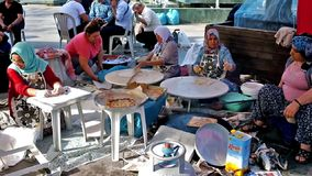 Turkish traditional street food. ANTALYA, TURKEY - MAY 13, 2017: The group of women prepares gozleme local flat bread in the street during the fair in old town stock video