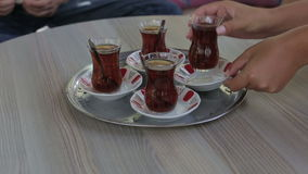 Turkish traditional tea ceremony. Female hand taking a cup of tea on the table stock video
