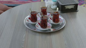 Turkish traditional tea ceremony. Female hands put a tray of cups on the table stock footage
