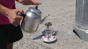 Turkish traditional tea ceremony. Male hand poured tea from a teapot into a cup stock video