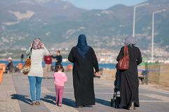 Turkish women in national dress and a little girl walking along the embankment royalty free stock photos