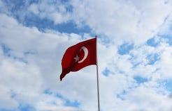 Turkisk flagga mot bakgrunden av sommarhimmel Arkivfoton