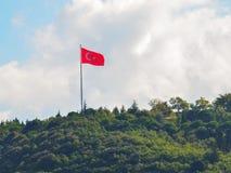 Turkisk flagga på en grön skogsbevuxen kulle på en bakgrund av moln och clouse för blå himmel upp arkivfoton