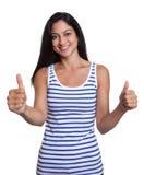 Turkisk kvinna i en randig skjorta som visar båda tummar Arkivbilder