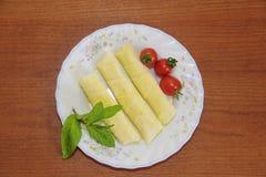 Turkiska pajer, tomater och gr?na mintkaramellsidor p? en platta royaltyfri foto