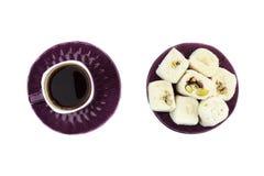 Turkiskt kaffe i purpurfärgad kopp och vit turkisk fröjd med pistaschen och valnöten på den purpurfärgade plattan på isoler arkivfoto
