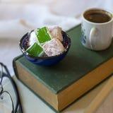 Turkiskt kaffe med turkisk fröjd som vilar på två böcker Arkivfoto