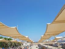 Turkiskt sandpappra med solparaplyet och solstolar, folk som garvar Arkivfoto