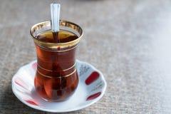 Turkiskt te i exponeringsglas för traditionell stil med skeden på tabellen Royaltyfria Foton