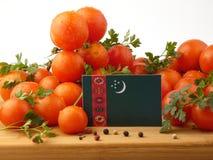 Turkmenistan-Flagge auf einer Holzverkleidung mit den Tomaten lokalisiert auf a Stockfoto
