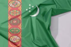 Turkmenistan tkaniny flaga zagniecenie z biel przestrzenią i krepa fotografia stock