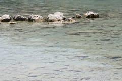 Turkoois blauw meerwater met witte stenen onder en hierboven Stock Fotografie
