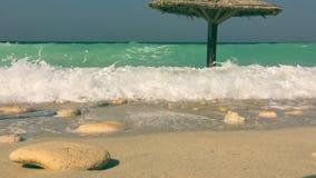 Turkoois golvenzeewater en schuim op zandig strand tijdens getijde op kust stock videobeelden