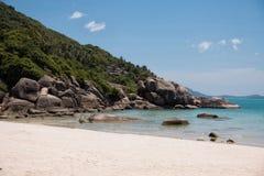 Turkoois water, granietrotsen en tropische bomen in het witte zand stock afbeelding