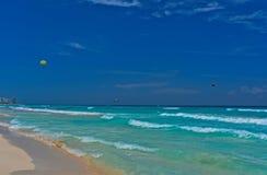 Turkoois water, zandig strand, blauwe hemel en het parasailing op de achtergrond stock afbeelding