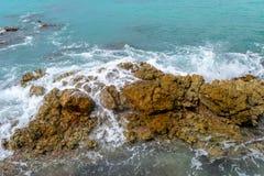 Turkoois zeewater die op rotsen op zonnige de zomerdag verpletteren stock afbeelding