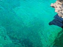 Turkoois zeewater met rots Stock Afbeeldingen