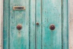 Turkooise deuren met klomphandvatten Stock Foto's